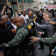 BALTIMORE, MD - MAY 23:  Baltimore City Sheriff's Deputies surround and protect Baltimore Police Officer Edward Nero's family members as demonstrators and members of the news media crowd around outside the Mitchell Courthouse-West after Nero was found not guilty on all charges against him related to the arrest and death of Freddie Gray May 23, 2016 in Baltimore, Maryland. One of six police officers charged, Nero was found not guilty by Baltimore Circuit Judge Barry Williams in a bench trial.  (Photo by Chip Somodevilla/Getty Images)