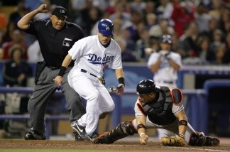 Paul Lo Duca, No. 16 of the Los Angeles Dodgers, is out at home plate as Javy Lopez, No. 18 of the Baltimore Orioles, keeps his foot on home plate in the fourth inning as home plate umpire Kerwin Danley makes the call on June 17, 2004 at Dodger Stadium.