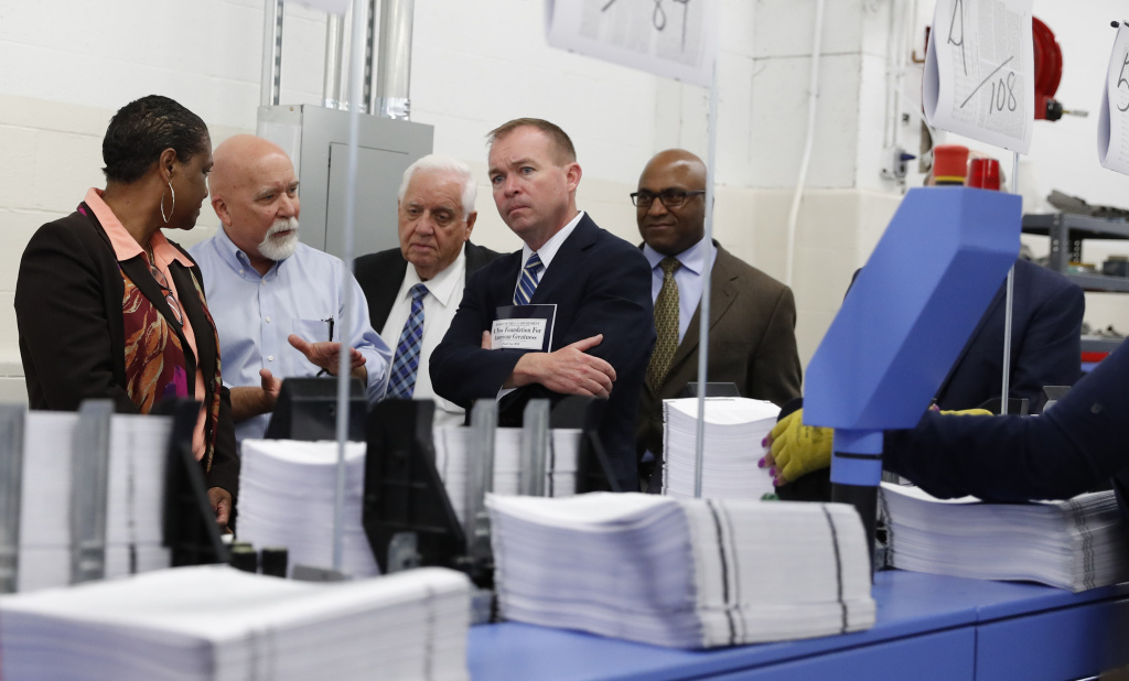 White House Budget Director Mick Mulvaney (second from right) holds a copy of the president's 2018 budget at the Government Publishing Office's plant in Washington, D.C. Mulvaney describes the plan as