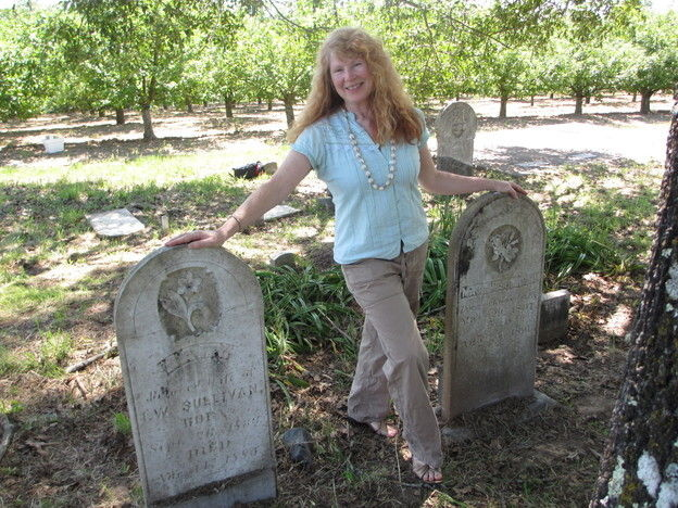 Jean McNear Powers stands between the twin headstones for her great-, great-, great-grandparents — pioneer couple Isaac and Polly Sullivan.