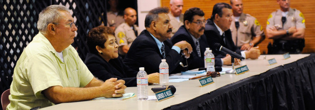 (L-R) City of Bell council members Lorenzo Velez, vice mayor Teresa Jacobo mayor Oscar Hernandez, coucilmen George Mirabel, and Luis Artiga, listen to residents asking them to resign during a council meeting on July 26, 2010 in Bell, California. The council members have voted to cut their salaries in response to public outcry at city officials' high salaries.