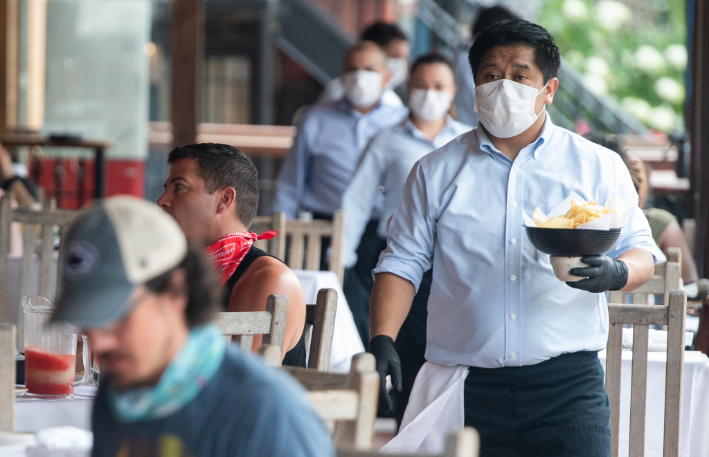 A waiter wearing a mask and gloves delivers food to a table to customers seated at an outdoor patio at a restaurant in Washington, DC, May 29, 2020.