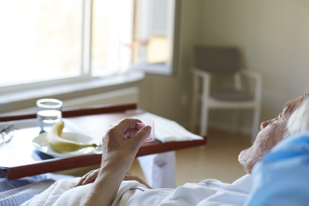 Senior man taking cough syrup while reclining on hospital bed