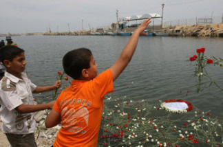 Palestinian boys throw flowers into the sea at Gaza City's port during a memorial for pro-Palestinian activists killed in an Israeli raid on aid ships bound for Gaza.