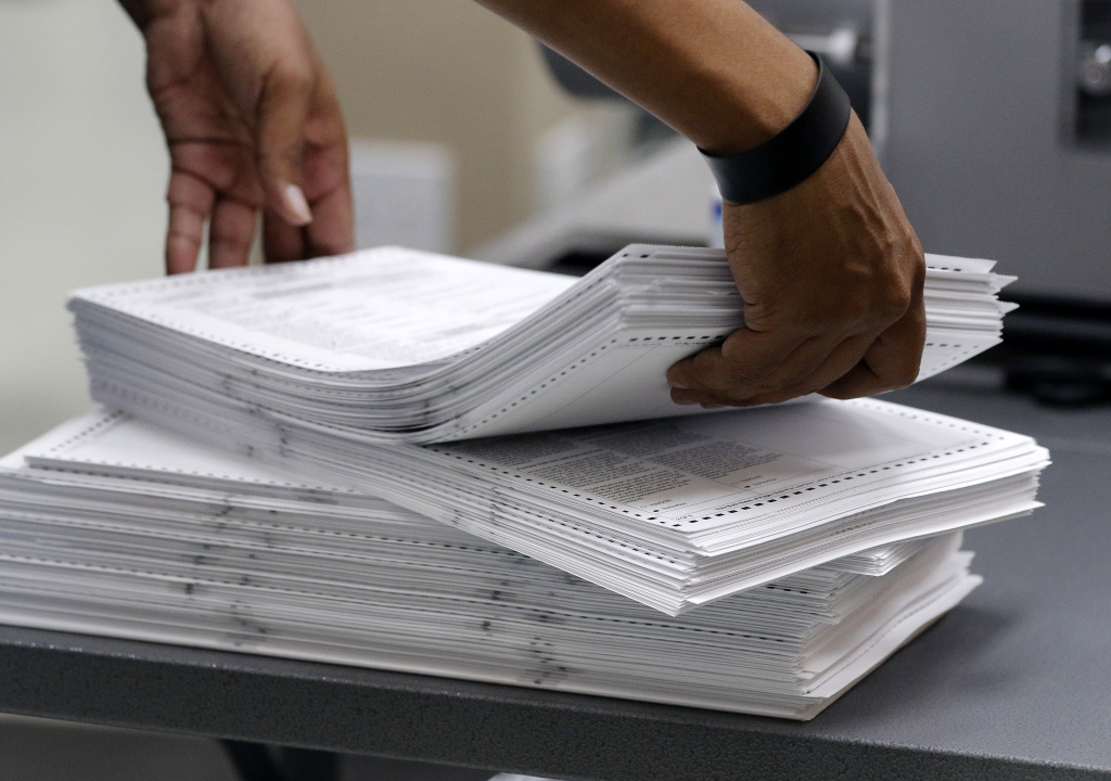Elections staff load ballots into machine as recounting is underway at the Broward County Supervisor of Elections Office on November 11, 2018 in Lauderhill, Florida. A statewide vote recount is being conducted to determine the races for governor, Senate, and agriculture commissioner.