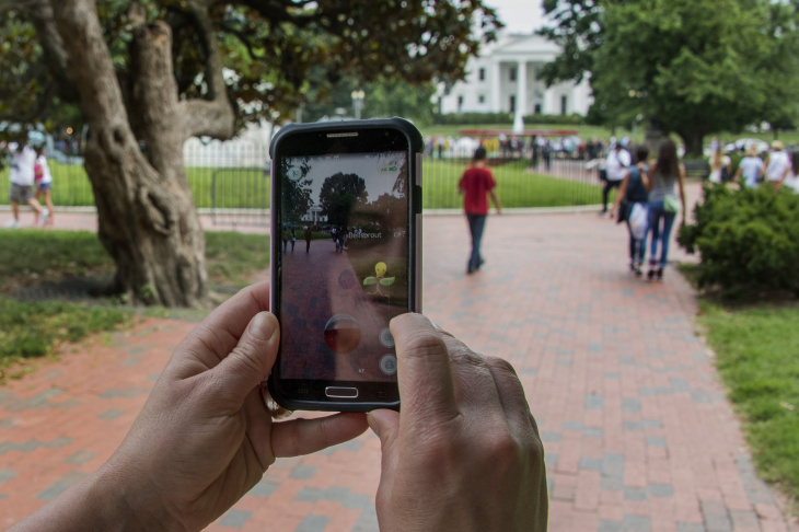 A woman holds up her cell phone as she plays the Pokemon Go game in Lafayette Park in front of the White House in Washington, DC, July 12, 2016. Pokémon Go mania is sweeping the US as players armed with smartphones hunt streets, parks, rivers and elsewhere to capture monsters and gather supplies in the hit game. The free application based on a Nintendo title that debuted 20 years ago has been adapted to the mobile internet Age by Niantic Labs, a company spun out of Google last year after breaking ground with an