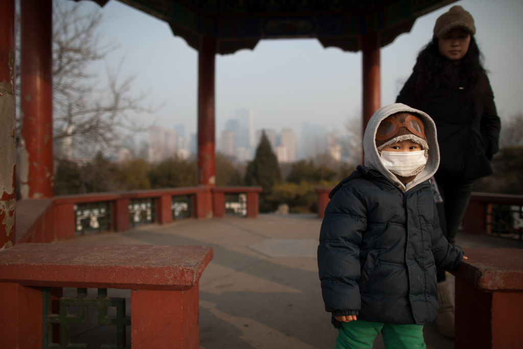 A child wearing a mask walks in a park in Beijing on January 15, 2013. Public anger in China at dangerous levels of air pollution, which blanketed Beijing in acrid smog, spread as state media queried official transparency and the nation's breakneck development.