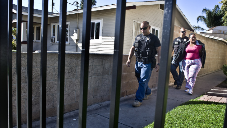 After arresting Toya Latrice Daniels,  Buena Park police officer James Woo, right, walks Daniels out her home and to his patrol car for transportation to the Buena Park Police Department. Daniels was charged with one misdemeanor count of contributing to the delinquency of a minor and one misdemeanor count of failure to reasonably supervise or encourage school attendance. By March of the school year, her elementary school child had accumulated 17 unexcused absences.