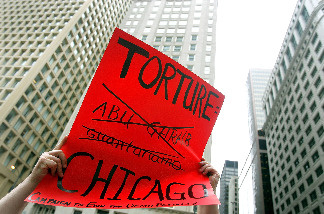 Adam Turl displays his sign regarding police torture during a demonstration July 21, 2006 in downtown Chicago, Illinois.