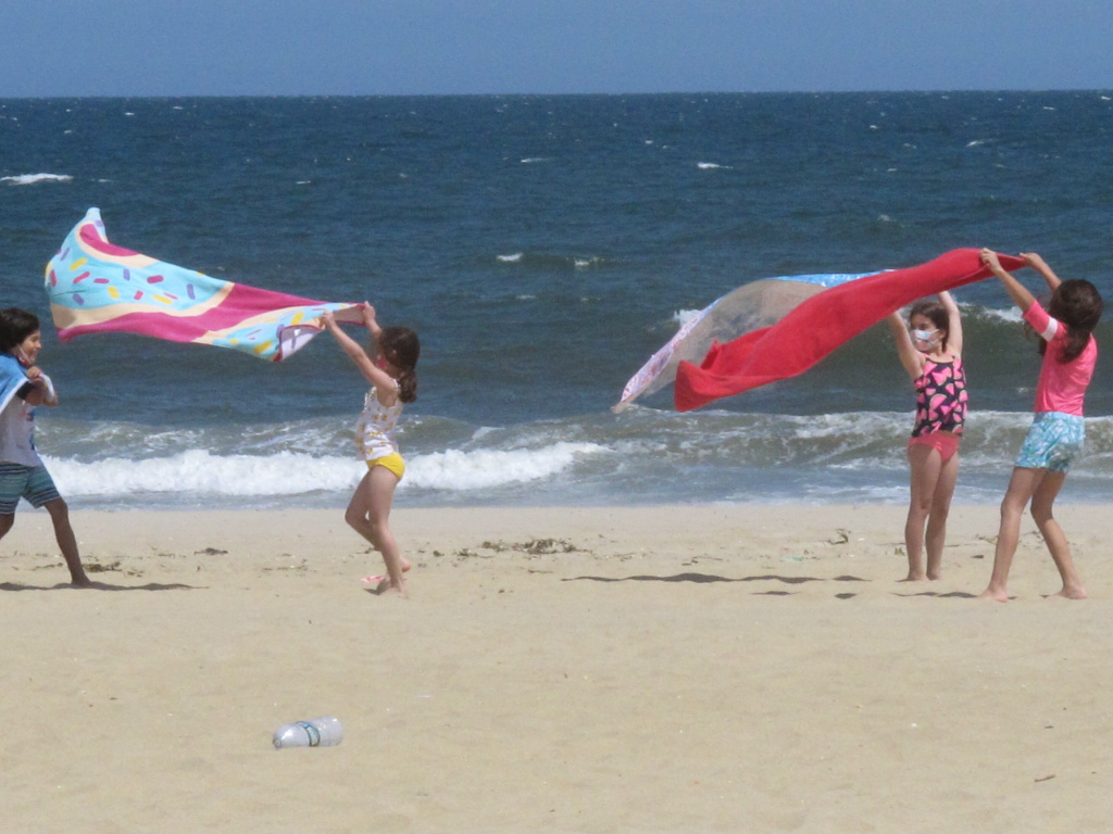 Children play with beach towels on a windy day in Belmar, N.J., on Tuesday. Millions are expected to hit the road or board a plane to celebrate Memorial Day weekend as more people get vaccinated and COVID-19 restrictions are scaled back.