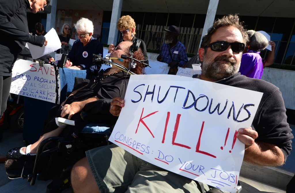 Activists with the California Alliance for Retired Americans hold placards while gathered for a die-in to protest the government shutdown and possible effects on senior citizens in front of the Federal Building in Los Angeles on October 16, 2013.