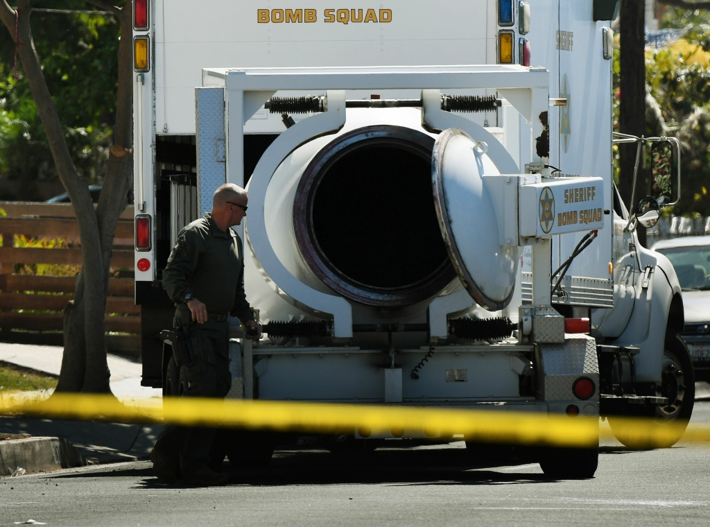 A Los Angeles County Sheriff's deputy checks the contents of a bombproof container beside a Lawndale house where several artillery shells and grenades were found on September 29, 2017.
