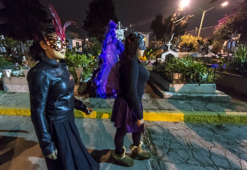 Two young women in costumes pass through graves at the San Francisco Cemetery in Mexico City on November 1, 2016.