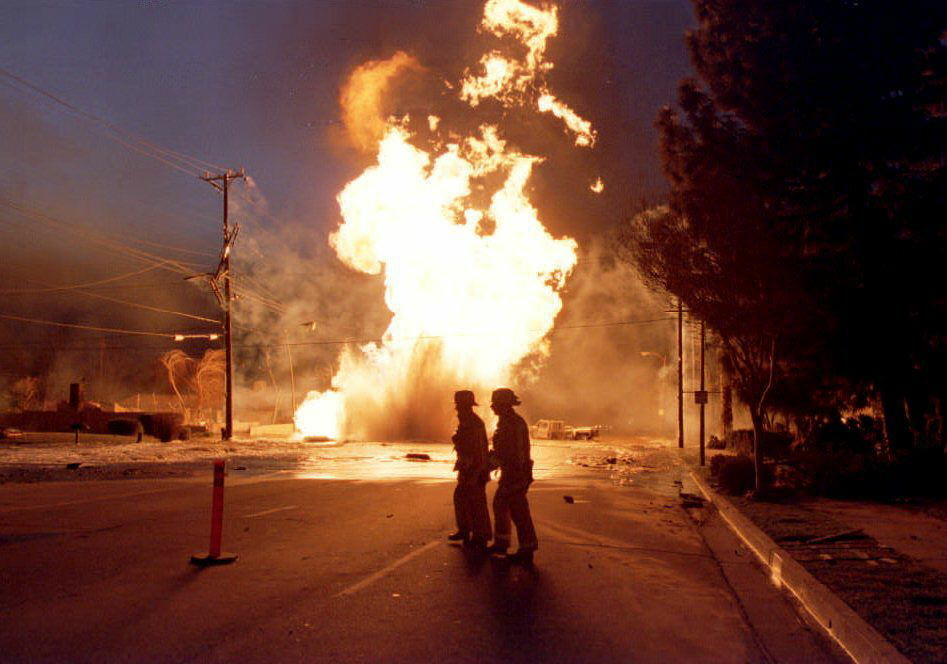 Firemen cross a street as a broken 16-inch gas main burns in the background, 17 January 1994, after an earthquake, measuring 6.6 on the Richter scale, struck the San Fernando Valley area. Officials confirmed 28 deaths resulting from the quake.