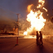 Firemen cross a street as a broken 16-inch gas mai