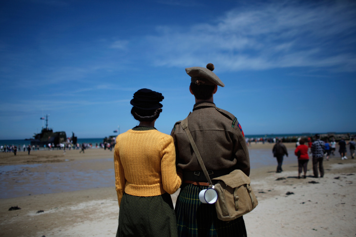 People wearing WWII style clothes look toward the sea, on the beach of Arromanches, western France , Friday June 6, 2014.  Ceremonies to commemorate the 70th anniversary of D-Day are drawing thousands of visitors to the cemeteries, beaches and stone-walled villages of Normandy this week, including some of the few remaining survivors of the largest sea-borne invasion ever mounted.