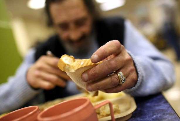 A man named R.J. holds a piece of bread as he eats a free meal provided by St. Anthony foundation on September 16, 2010 in San Francisco, California. The U.S. poverty rate is higher than previously thought.