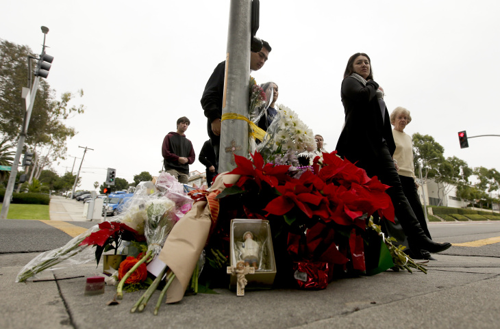 Church goers pass by a makeshift memorial Thursday, Dec. 18, 2014 near where a driver suspected of being intoxicated hit a group of pedestrians and another car outside a church as a Christmas service ended Wednesday night in Redondo Beach, Calif. Three people were killed and several others were injured including five children, police said. Margo Bronstein, 56, was arrested after the crash on suspicion of driving under the influence and vehicular manslaughter, Redondo Beach police Lt. Shawn Freeman said.