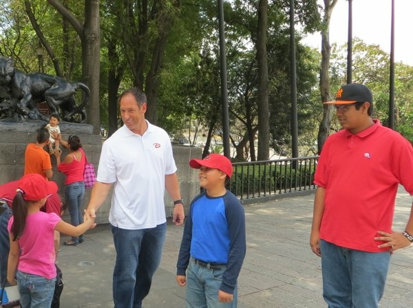 Luis Gonzalez of the Arizona Diamondbacks gives out team caps to children in Mexico City's biggest park.