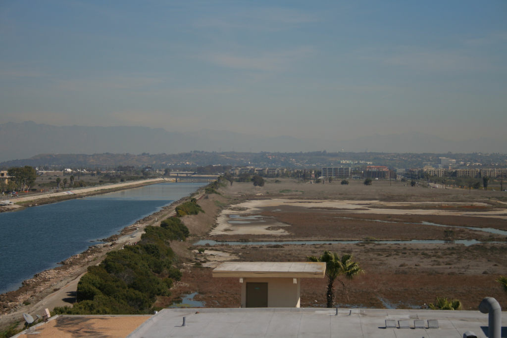 Water locked in a concrete channel could change dramatically the saltpan flats of the ecological reserve to the right.