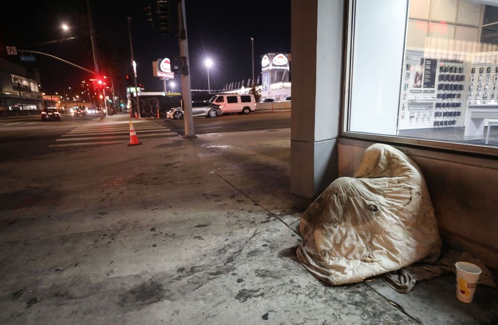 An unhoused person rests beneath a blanket on Sunset Boulevard amid the COVID-19 pandemic on July 1, 2020 in Los Angeles, California.