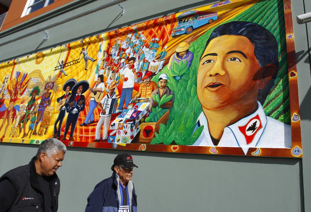 Men walk underneath a mural depicting Cesar Chavez along Cesar Chavez street in the Mission District of San Francisco.