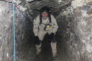In this Thursday, Nov. 25, 2010 photo released by U.S. Immigration and Customs Enforcement (ICE), a task force agent crouches inside a cross-border tunnel that authorities say was used as an underground drug passage, in San Diego. The tunnel found Thursday is 2,200 feet long, more than seven football fields, and runs from the kitchen of a home in Tijuana, Mexico, to two warehouses in San Diego's Otay Mesa industrial district, said Mike Unzueta, head of investigations at U.S. Immigration and Customs Enforcement in San Diego.