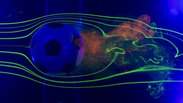 A close up of the Brazuca ball in NASA's Ames Fluid Mechanics Laboratory. Smoke highlighted by lasers visualizes air flow around the ball.