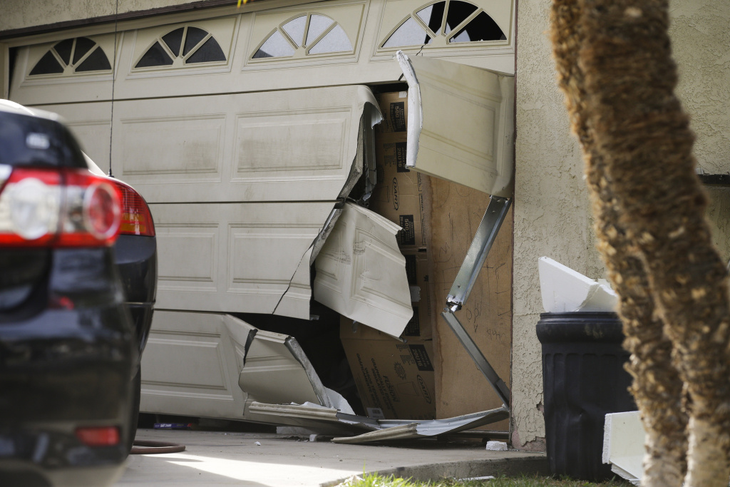 A garage door of Enrique Marquez's home is seen broken in a recent FBI raid, Wednesday, Dec. 9, 2015, in Riverside, Calif. Authorities have said Enrique Marquez, an old friend of San Bernardino attacker Syed Farook, purchased two assault rifles used in last week's fatal shooting that killed 14 people.