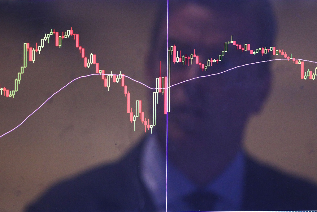 A trader is reflected in a market screen on the floor of the New York Stock Exchange (NYSE) in New York City.