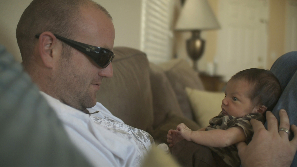 A veteran and his newborn son, in a scene from the PBS film, Of Men and War. (Photo courtesy of Alice Films.)