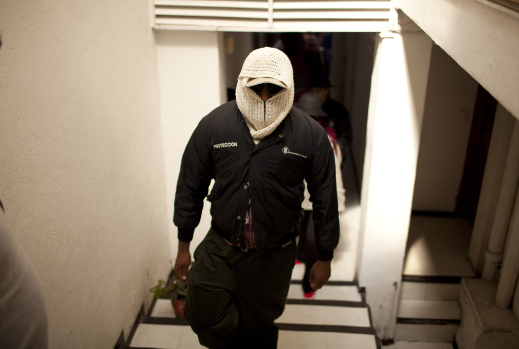 In this file photo, a masked family member of a self-defense squad from the town of Aquila arrives for a press conference in Mexico City, Monday, Aug. 19, 2013. The group claimed they took up arms to defend themselves from the Knights Templar drug cartel, which demanded to be given 700,000 pesos ($54,000) that the townspeople earned from mining royalties. This month, federal officials confirmed Mexican drug cartels have entered the country's lucrative mining industry.