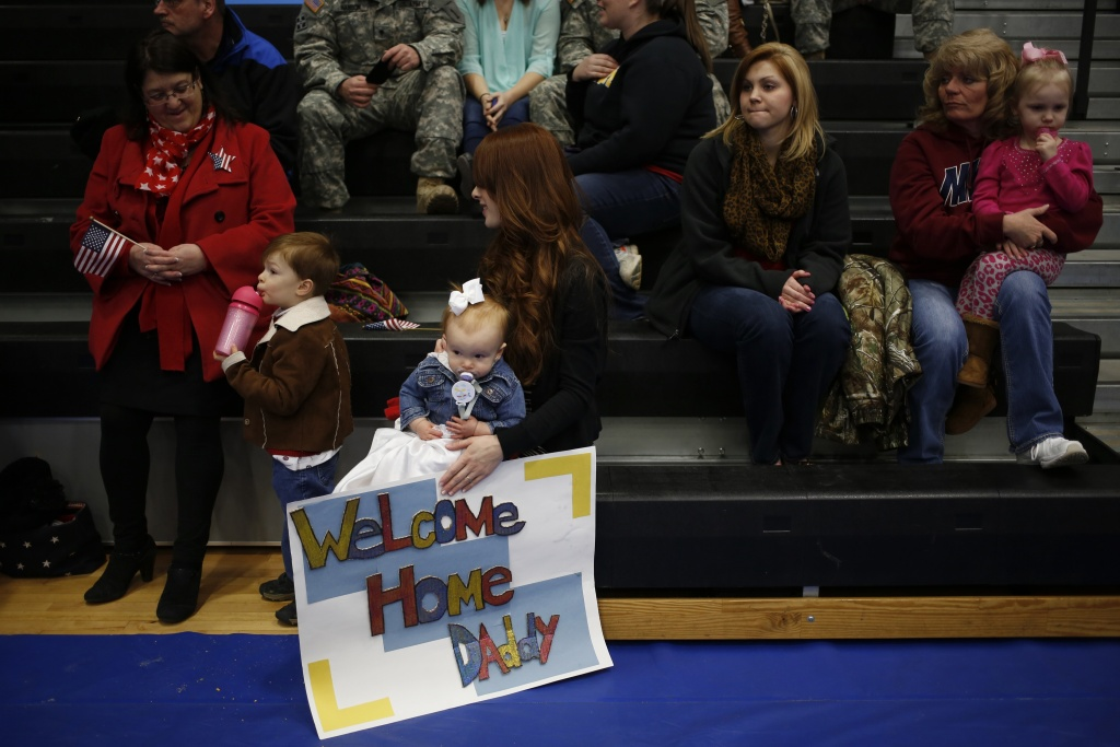 Army wife  (C) holds her daughter Annalise and a welcome home sign while waiting to greet her husband Spc. Eric Henry of the U.S. Army's 3rd Brigade Combat Team, 1st Infantry Division, during a homecoming ceremony in the Natcher Physical Fitness Center on Fort Knox on February 27, 2014 in Fort Knox, Kentucky. About 100 soldiers returned to Fort Knox after a nine-month combat deployment conducting village stability operations and working alongside Afghan military and police forces.