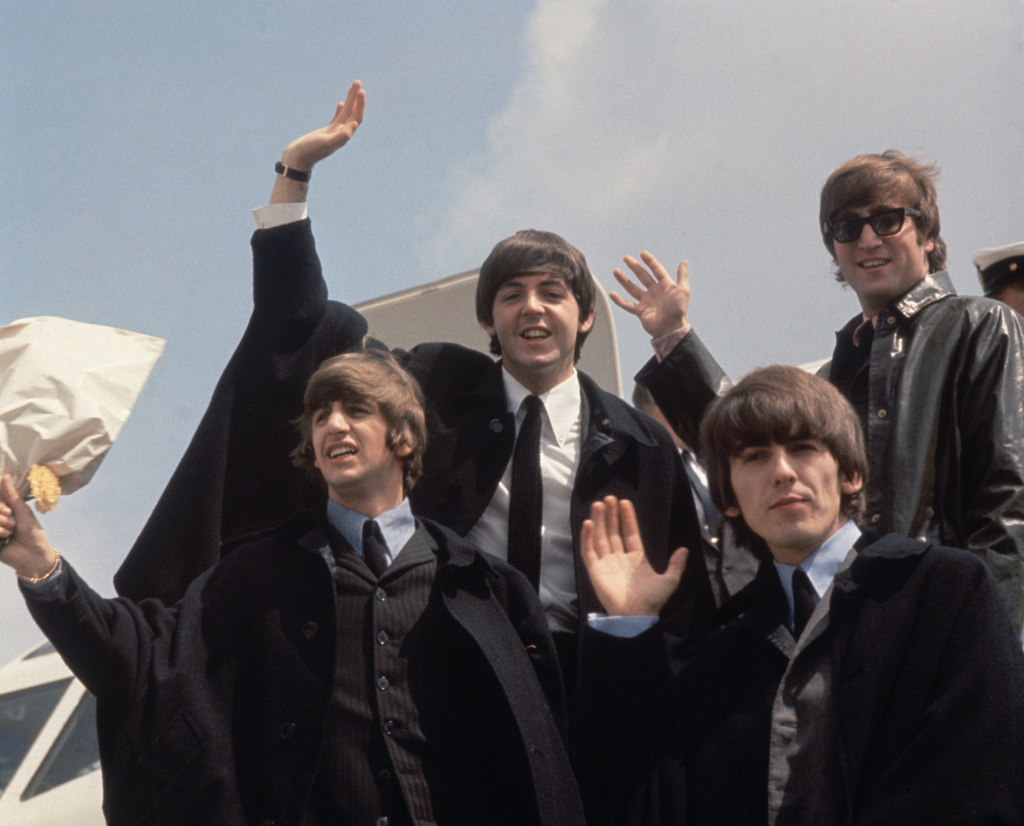 2nd July 1964:  The Beatles (from left to right, John Lennon (1940 - 1980), George Harrison (1943 - 2001), Paul McCartney and Ringo Starr) arrive back at London Airport after their Australian tour. So what do you say--The Beatles or The Rolling Stones?
