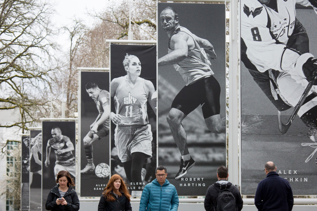 Employees walk past banners depicting athletes at Nike headquarters on March 22, 2018 in Beaverton, Ore.