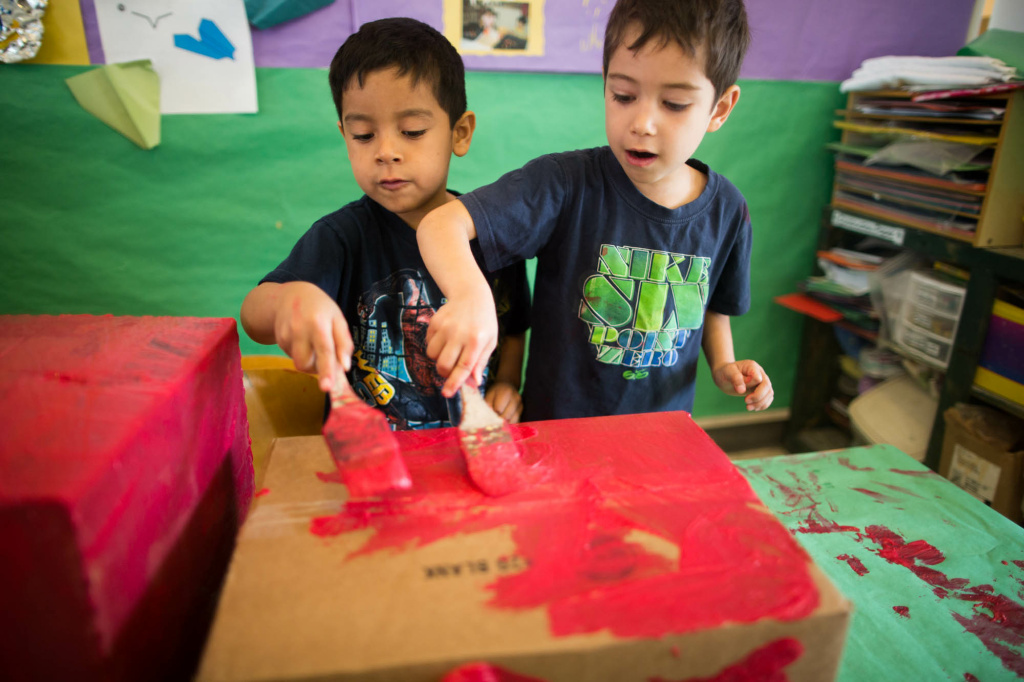 Tupac (left) and Alessandro paint boxes the color of a fire truck. The two are students at University Village, one of three pre-schools run by UCLA Early Care and Education.