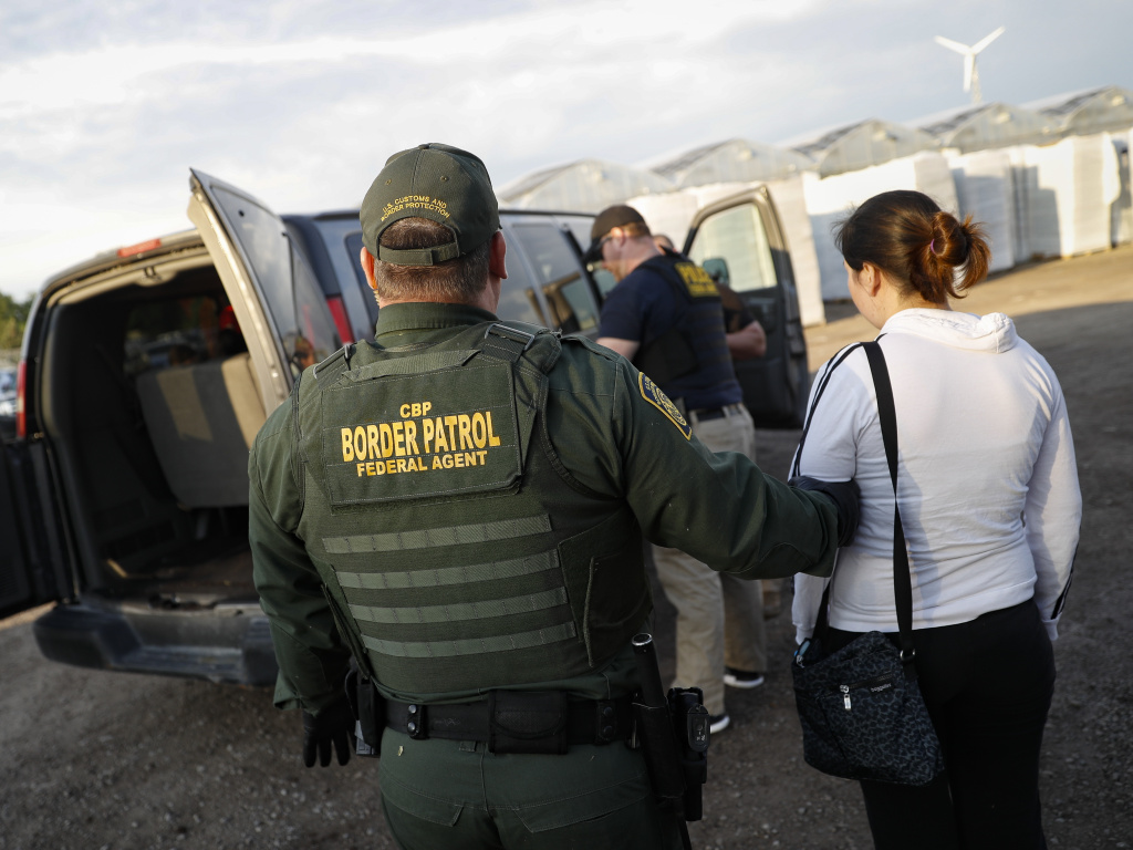 Government agents apprehend suspects during an immigration sting at Corso's Flower and Garden Center Tuesday in Castalia, Ohio. It's one of the largest against employers in recent years on allegations of violating immigration laws.