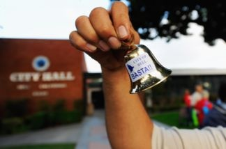 A resident celebrates the arrest of eight former and current Bell city officials by shaking little bells in front of City Hall on Sept. 21, 2010. The city officials were charged with misappropriation of more than $5.5 million in public funds for excessive salaries and illegal personal loans.