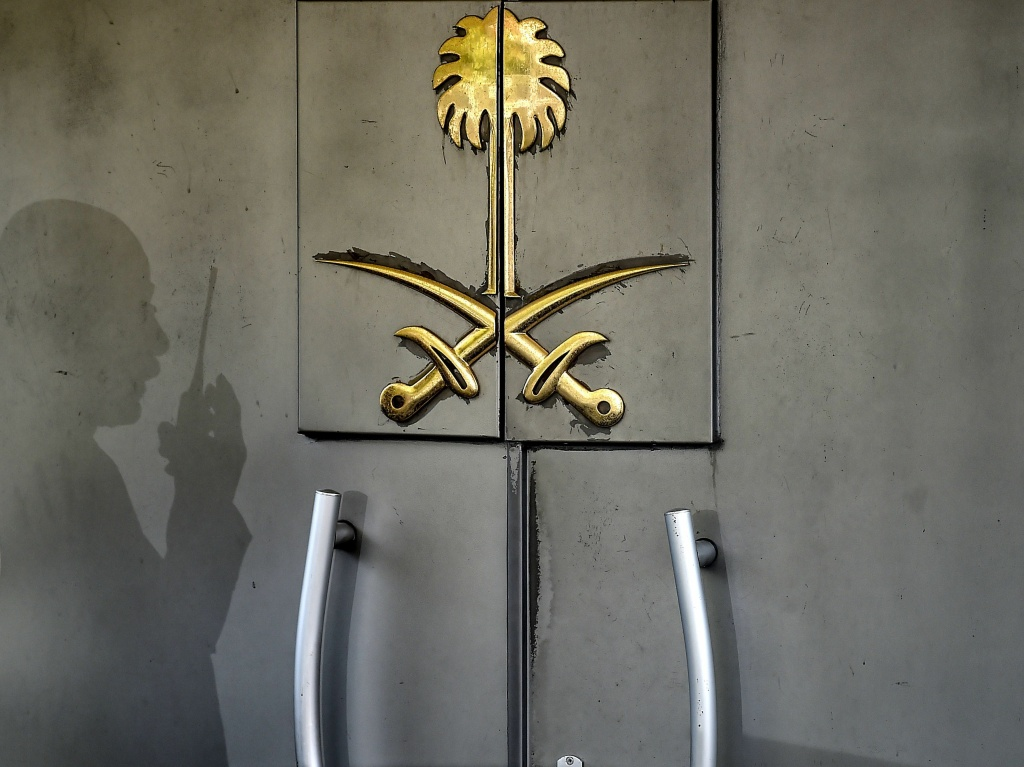 The shadow of a security member of Saudi Arabia's consulate in Istanbul is seen on the door of the building, Nov. 1. The top Saudi prosecutor says Jamal Khashoggi was murdered at the diplomatic facility.