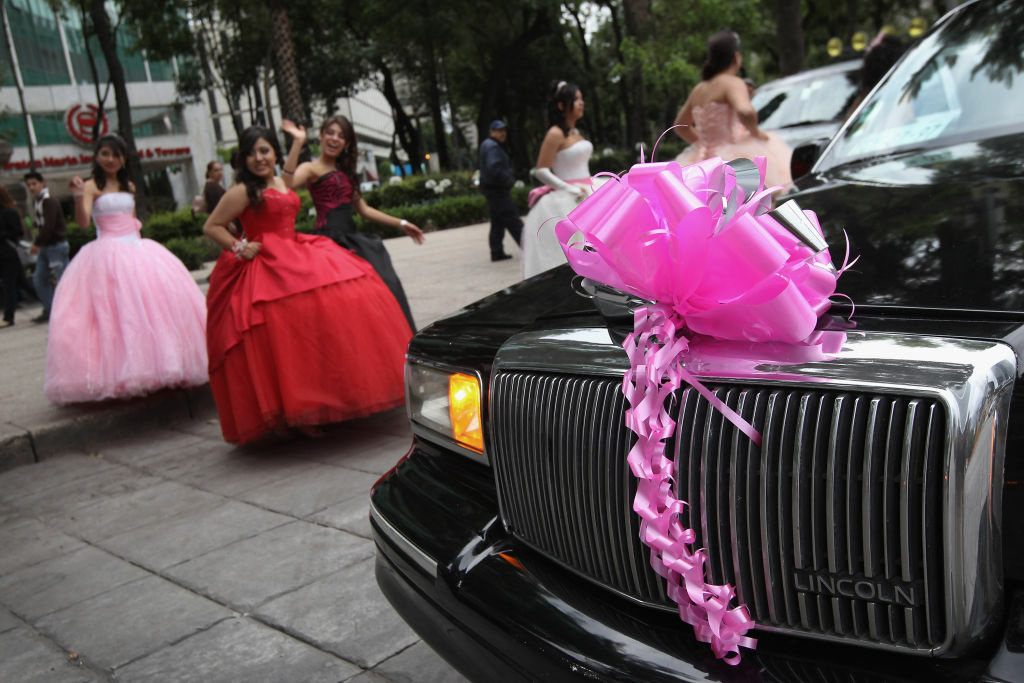 Fifteen-year-old girls return to their limousine after a photo shoot at Mexico's Angel of Independence monument on June 23, 2012 in Mexico City, Mexico.