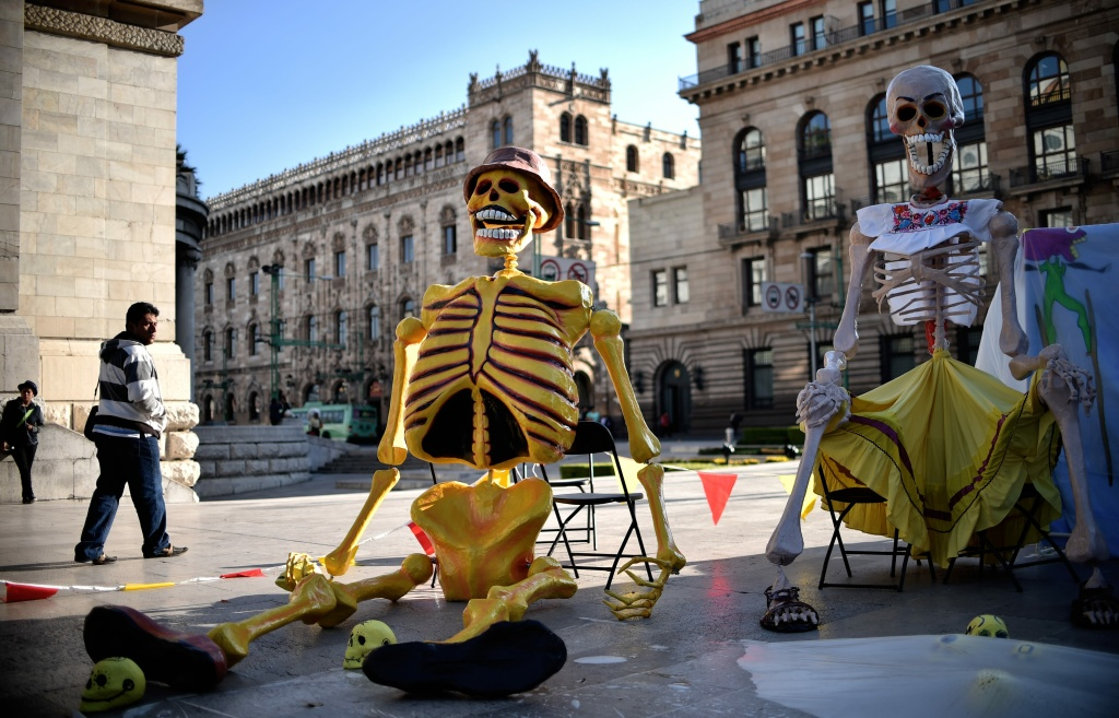 A man passes next to fake giant skeletons placed in an altar in front of the Fine Arts Palace for Day of the Dead in Mexico City on November 1, 2016.