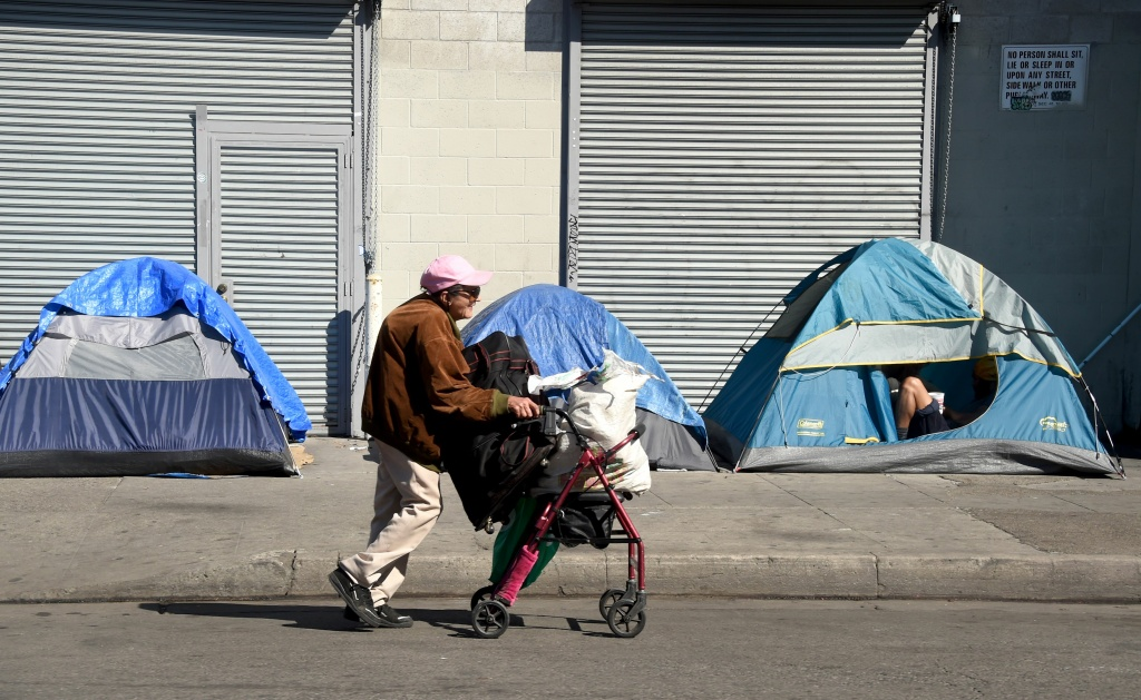 A woman pushes her walker past tents housing the homeless in Los Angeles, California on February 9, 2016.