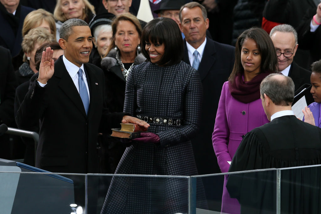 U.S. President Barack Obama (L) is sworn in during the public ceremony by Supreme Court Chief Justice John Roberts as First lady Michelle Obama, and daughters, Sasha Obama and Malia Obama look on during the presidential inauguration on the West Front of the U.S. Capitol January 21, 2013 in Washington, DC.   Barack Obama was re-elected for a second term as President of the United States.