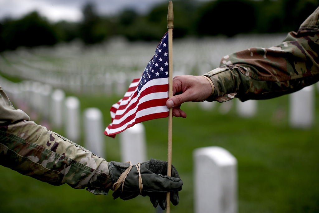 Sgt. Iwona Kosmaczewska (L) and Pvt. 2 Wesley Defee (R), members of the 3rd U.S. Infantry Regiment, place flags at the headstones of U.S. military personnel buried at Arlington National Cemetery, in preparation for Memorial Day May 25, 2017 in Arlington, Virginia.