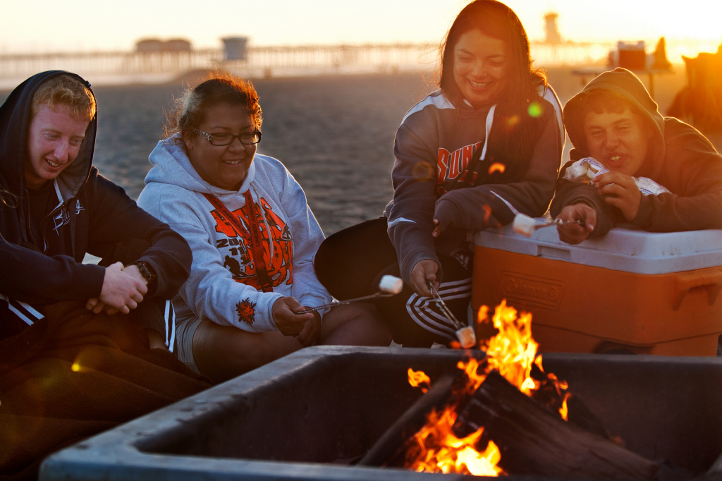Jerry Wymore, Paige Brown, Sabrina Fuentes, and Nick Kern of Apple Valley roast marshmallows in this June 6, 2013 file photo taken at a fire pit in Huntington Beach. The Newport Beach City Council voted Tuesday, January 13, 2014, to bring back wood-burning at at least 15 of the city's beach fire rings.