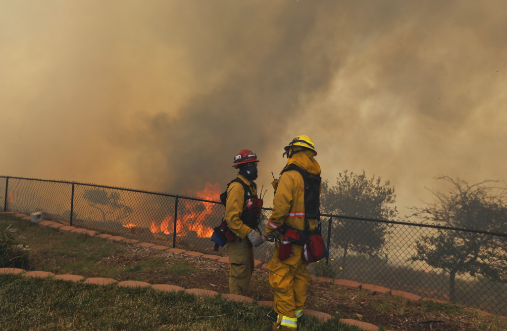 Two firefighters discuss a strategy change while fighting a wildfire from the backyard of a home Thursday, May 15, 2014, in San Marcos, Calif. Gusty winds failed to return Thursday in San Diego County wildfire areas and authorities said it was a window of opportunity to make further gains against flames that have charred thousands of acres and burned homes.