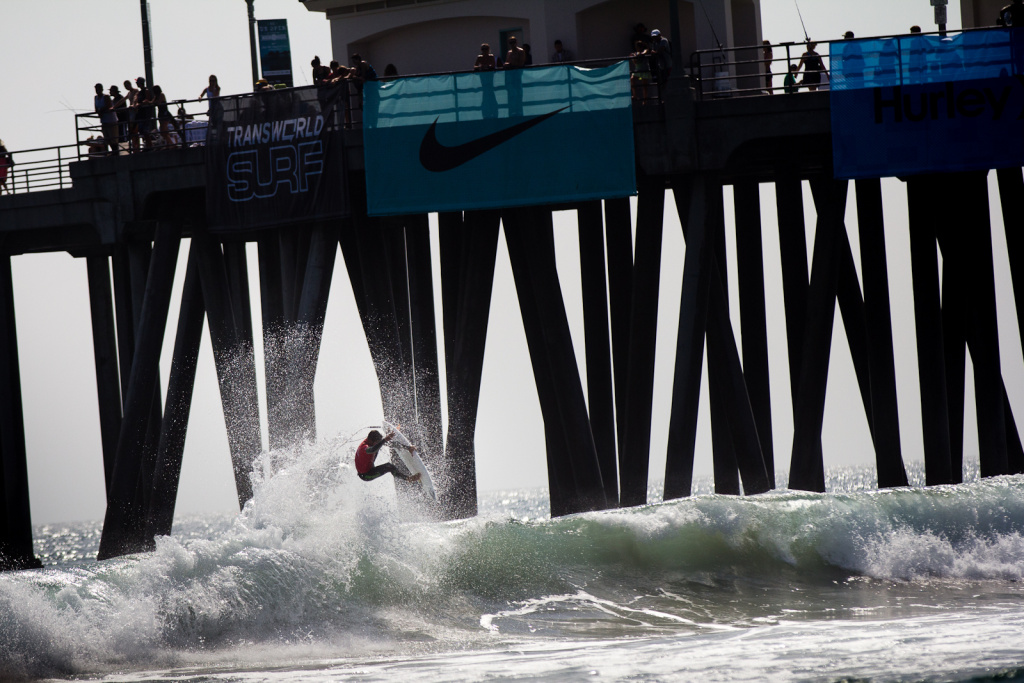 A surfer catches air near the Huntington Beach pier during the U.S. Open of Surfing competition on Friday, August 3, 2012.