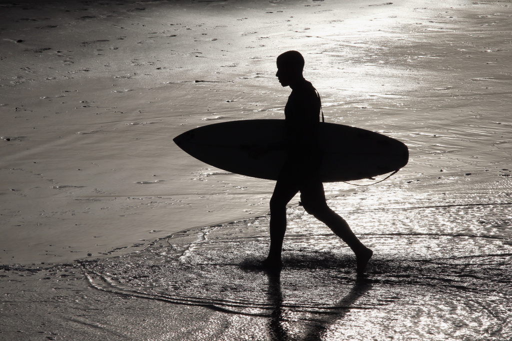 A California recreational surfer prepares to go surfing on March 18, 2014.