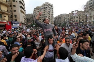 Protesters chant slogans as they march following an attack by security forces in Tahrir Square, in Cairo, Egypt, Saturday, April 9, 2011. Demonstrators burned cars and barricaded themselves with barbed wire inside a central Cairo square demanding the resignation of the military's head after troops violently dispersed an overnight protest killing one and injuring scores.