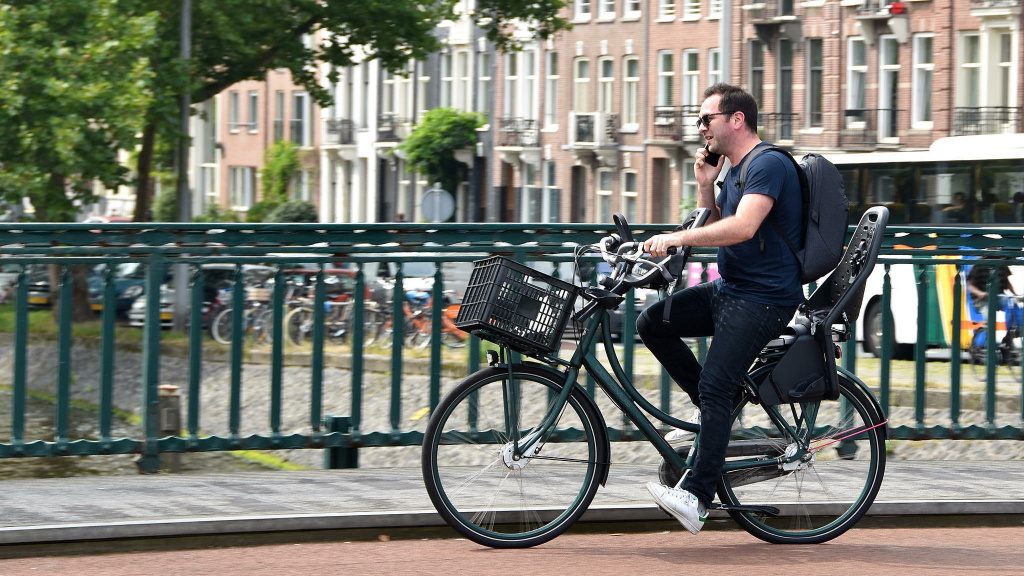 A man talks on the phone while he rides a bike in Amsterdam. Legislation proposed in the Netherlands would impose a fine on bicyclists who use a mobile phone while they're on their bikes.